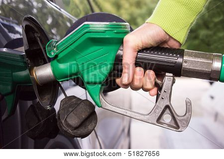 Hand with hose filling car tank with gasoline