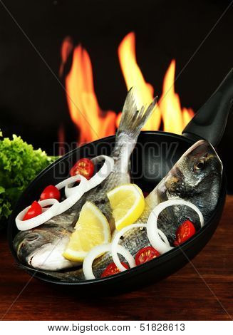 Dorado fish on table on fire background