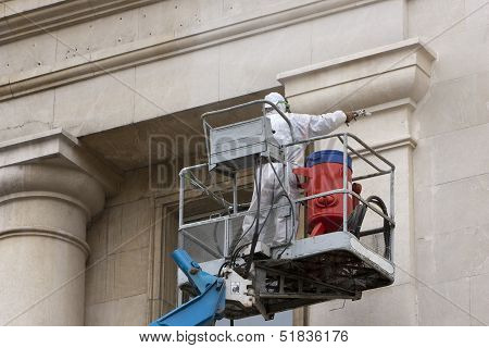 Worker In Platform Washing A Building