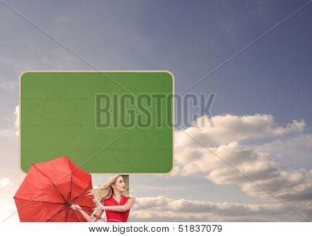 Composite image of beautiful woman posing with a broken umbrella in front of road sign in the sky