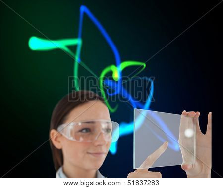 Composite image of doctor in protective glasses holding virtual screen on black background with glowing blue and green lines
