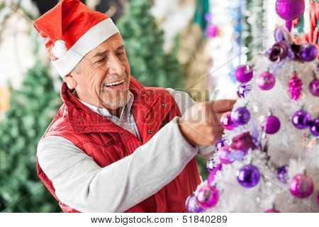 Happy male owner in Santa hat decorating Christmas tree at store