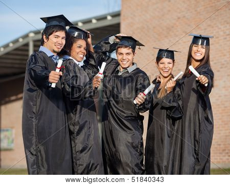 Portrait of multiethnic graduate students holding certificates on university campus