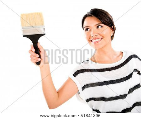 Woman painting with a brush and smiling - isolated over white background
