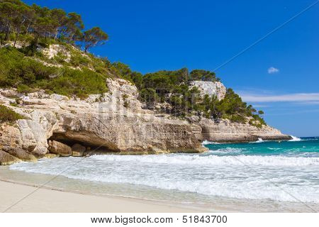 Mediterranean sea cliffs at Cala Mitjana beach at Menorca island, Spain.