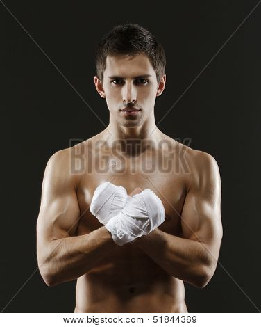 Half-length portrait of exercising fighter with hands wrapped with elastic bandage, isolated on black