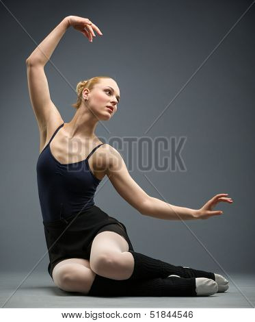 Dancing on the floor ballerina with her hand up, isolated on grey. Concept of elegant art and sportive hobby
