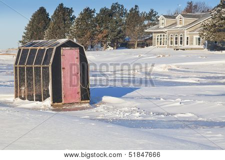 Rustic ice fishing shack out on the ice.