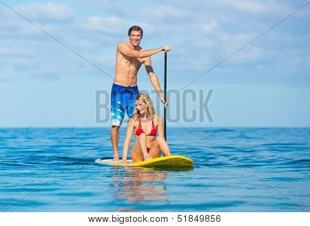Couple Stand Up Paddle Surfing In Hawaii, Beautiful Tropical Ocean, Active Beach Lifestyle