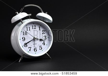 Beautiful White Old Fashion Alarm Clock Against Black Background, With Copy Space For Your Text Here