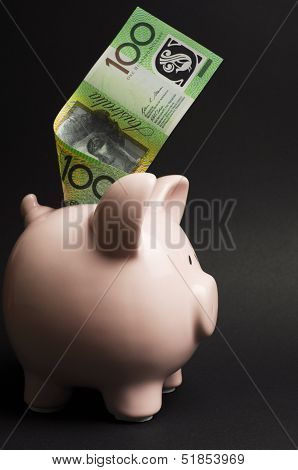 Pink Piggy Bank With Australian Money Against A Black Background, For Savings Concept, With 100 Doll