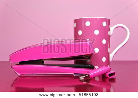 Pretty In Pink Office Accessories, Stapler, Pen Drive, And Polka Dot Mug, On A Pink Desk Against A P