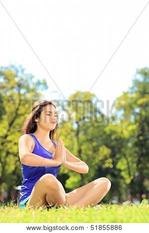 Young female athlete in sportswear doing yoga exercise seated on a green grass in a park