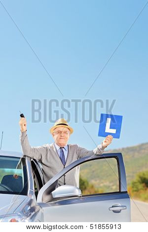 Happy mature man next to car holding a L sign and car key after having his driver's licence, outside