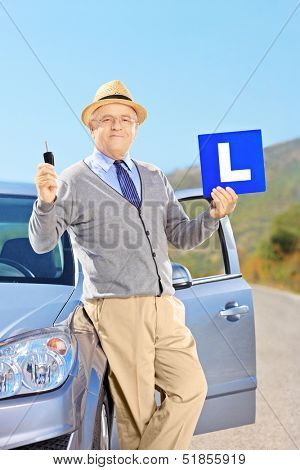 Smiling mature man on his car holding a L sign and car key after having his driver's licence, outside