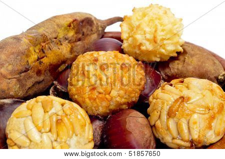 some panellets and roasted chestnuts and sweet potatoes, typical snack in All Saints Day in Catalonia, Spain, on a white background
