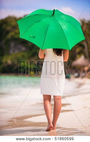 Back view of young woman with green umbrella on the beach