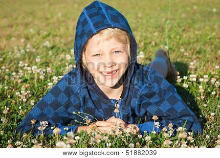 Smiling Young Boy Lying In Grass Smiling