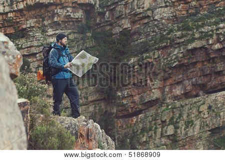 Man with map exploring wilderness on trekking adventure