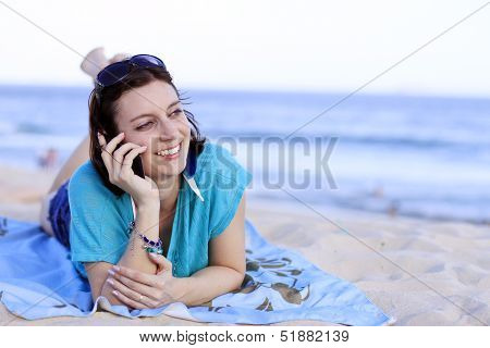 Woman talking on cell phone at beach