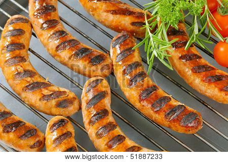 oily grilled sausages with vegetable, on a grilling grid