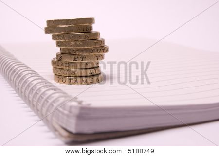 Stack Of One Pound Coins On A Notebook