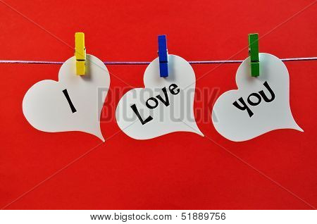I Love You Message Across Three White Hangning Hearts From Colorful Pegs Against A Red Background, A