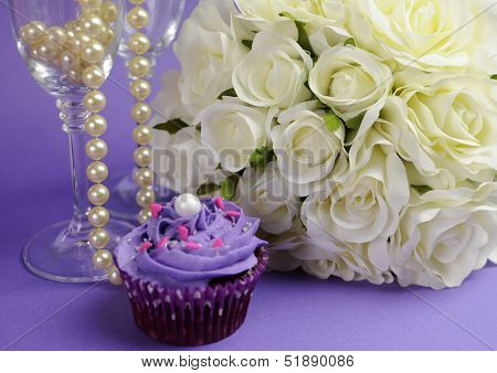 Wedding Bouquet Of White Roses With Purple Cupcake And Pearls In Champagne Glass, Against Purple Lil