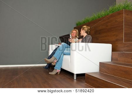Two, casually dressed, business women during an informal presentation, in discussion on a white leather couch in a modern open office space