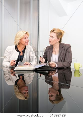 Two senior business women meeting in a modern meeting room
