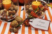 stock photo of centerpiece  - Happy Halloween tag message with orange candles and nuts centerpieces with pumpkin jack o lantern decorations.