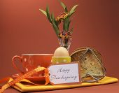 stock photo of heartfelt  - Happy Thanksgiving breakfast for your special one with toast and egg with coffee or tea in an orange polka dot cup and saucer with heartfelt gift tag and flowers in vase - JPG
