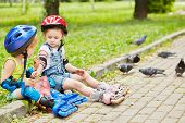 Little boy and girl in roller equipment sit on curb of walkway in summer park, eat bread and feed pi