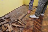 stock photo of rotten  - Worker demolishing oak parquet with crowbar tool - JPG