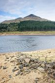 stock photo of water shortage  - the banks of a reservoir normally submerged due to a decrease in water levels after a dry summer has led to water shortage - JPG