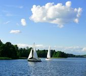 Постер, плакат: Yacht sailing towards sunset in blue background sunny background yacht in a lake at the evening