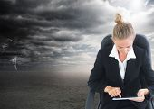 Composite image of blonde businesswoman sitting on swivel chair with tablet in front of stormy sky