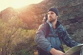 stock photo of survival  - portrait of adventure man with map and extreme explorer gear on mountain with sunrise or sunset - JPG