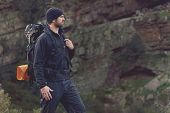 pic of survival  - Adventure man hiking wilderness mountain with backpack - JPG