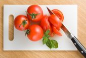 stock photo of cutting board  - Red tomatoes on hardboard with a knife - JPG