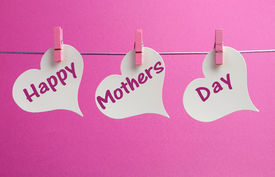 image of pegging  - Happy Mothers Day message greeting written acorss white heart tags hanging from pink pegs on a line against a feminine pink background - JPG