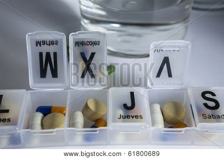Pills with pill organizer writing in Spanish