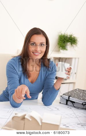 Brown Hair Female Architect Sitting At Office Holding Coffee