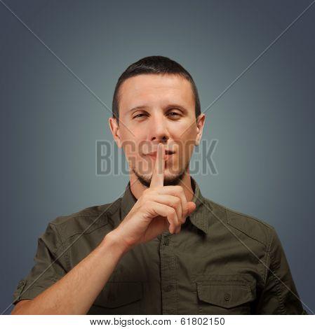 Man makes silence gesture