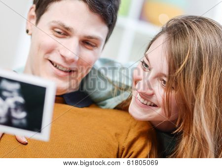 Beautiful Couple Watching With Emotion Ultrasound Pictures Of Their Baby