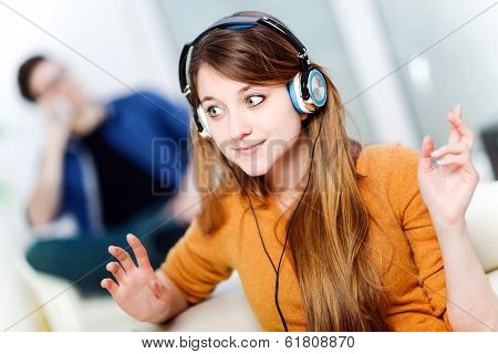 Beautiful Blond Listening To Some Music While Her Boyfriend Is Bored
