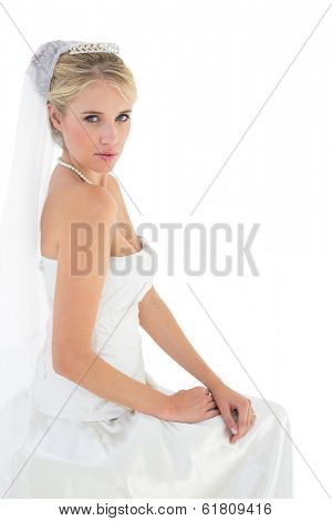Portrait of sensuous bride in off shoulder dress sitting against white background