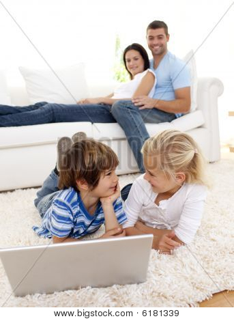 Friends Using A Laptop And Couple On Sofa