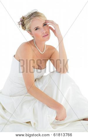 Portrait of sensuous bride sitting over white white background