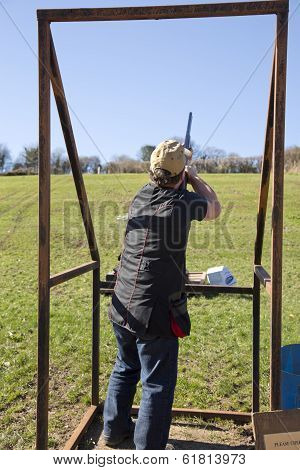 Clay Shooter In Stand Firing At The Clay